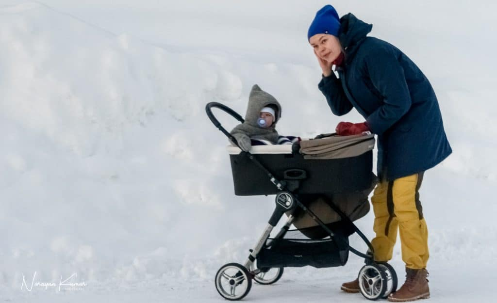 Mother, child and pram in snowscape at Tromso, Norway