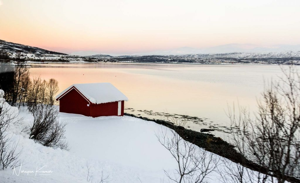 Red house in snow by the lake at Tromso, Norway