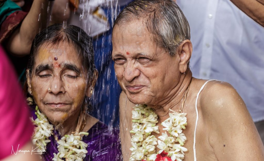 Old couple re-performing wedding rituals on the husband's 80th birthday